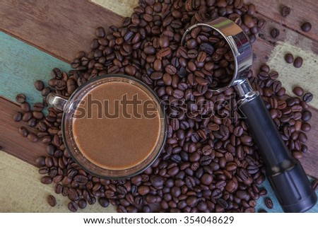 Cup of coffee with beans on wooden background - stock photo