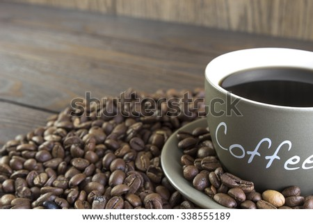Cup of coffee  with beans standing on a wooden table.  Crop, blurred, focus on mug - stock photo