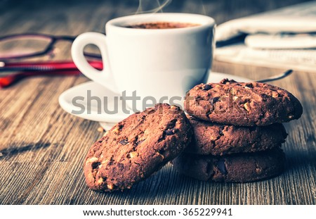 Cup of coffee with biscuit cookies and newspapper. Chocolate biscuit cookies. Chocolate cookies on white linen napkin on wooden table. Coffee break , breakfast. - stock photo