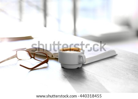 Cup of coffee with book and glasses on the table