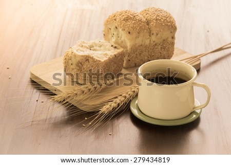 Cup of coffee with bread and dry wheat on the table - stock photo