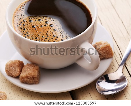 Cup of coffee with brown sugar on a light wooden table.