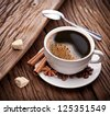 Cup of coffee with brown sugar on a wooden table. - stock photo