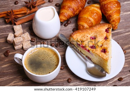 cup of coffee with cake with cranberries and croissants on a wooden background - stock photo