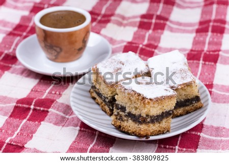 Cup of coffee with cakes on the plate.