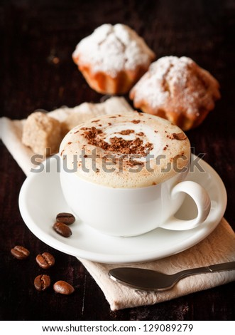 Cup of coffee with chocolate, coffee beans and muffins on a dark background.