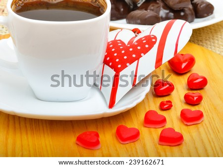 Cup of coffee with chocolate sweets a valentine heart on white plate on wooden background - stock photo