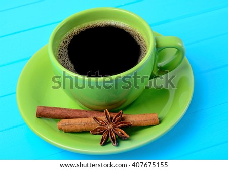Cup of coffee with cinnamon and anise on blue table - stock photo