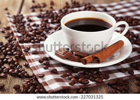 Cup of coffee with cinnamon and chocolate on brown wooden background - stock photo