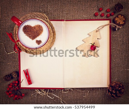 Cup of coffee with cinnamon hearts , wooden pine , pin, rowan and red book with space for your text on Christmas card.