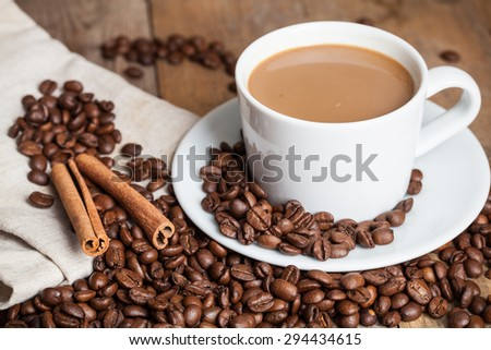 cup of coffee with cinnamon sticks on wood, rustic style