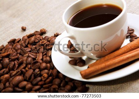 cup of coffee with cinnamon tubes and grains of coffee - stock photo