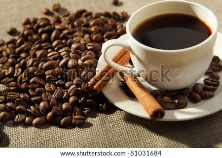 cup of coffee with cinnamon tubes and grains of coffee
