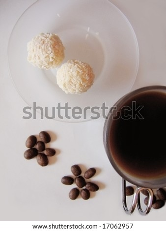 cup of coffee with coconut sweets and beans