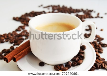 Cup of coffee with coffee beans and cinnamon stick
