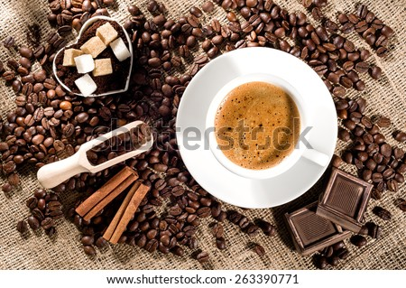 Cup of coffee with coffee beans, chocolate pieces, cinnamon sticks, white and brown sugar, and scoop on burlap background. - stock photo