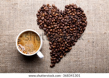 Cup of coffee with coffee beans in shape of heart on burlap background - stock photo