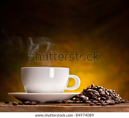 Cup of coffee with coffee beans on a beautiful brown background. - stock photo
