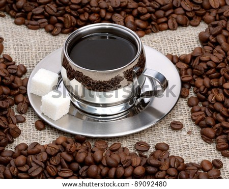 Cup of coffee with coffee beans on a beautiful brown background - stock photo