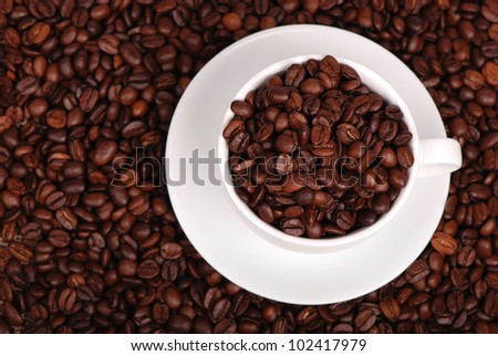 Cup of coffee with coffee beans on a beautiful brown background/Top view of coffee