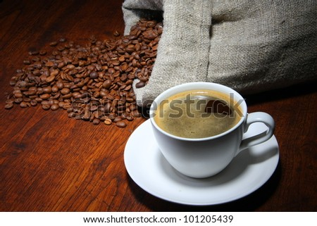 Cup of coffee with coffee beans on a beautiful wooden background. - stock photo