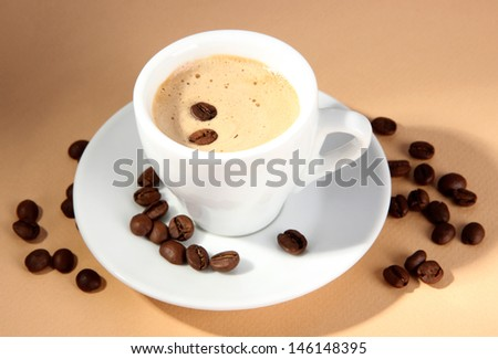 Cup of coffee with coffee beans on beige background - stock photo