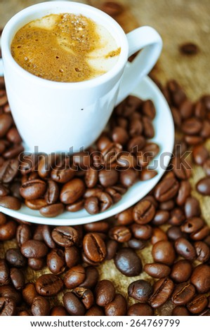 cup of coffee with coffee beans on the wooden background. Toned image - stock photo