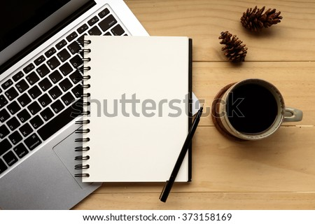 Cup of coffee with computer laptop and opened notebook on wooden desk, selective focus  - stock photo