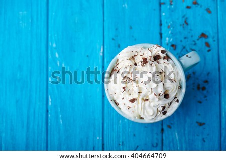 cup of coffee with cream and chocolate on blue wooden table. Close view. Top view - stock photo