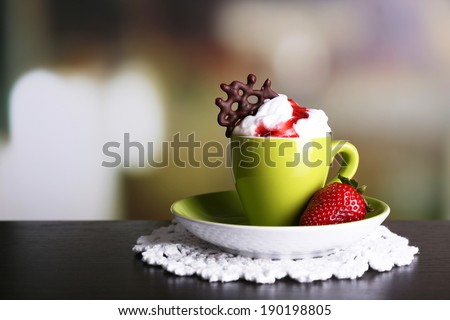 Cup of coffee with cream and strawberry sauce on color wooden table, on dark background