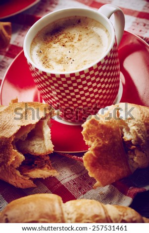 Cup of coffee with croissant on wooden background - stock photo