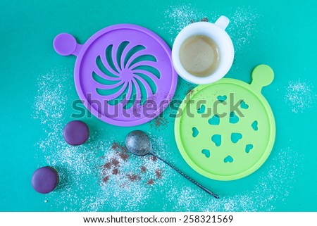 Cup of coffee with decorative stencils and purple mini macaron on cyan background dusted with coffee and sugar. - stock photo