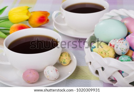 Cup of coffee with Easter candy on saucer next to a basket of eggs and candy