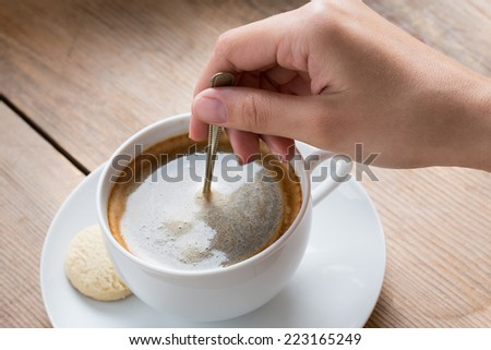 Cup of coffee with foam being stirred by a human hand - stock photo