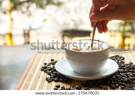 Cup of coffee with foam being stirred by a woman, handCappuccino stirred ,Coffee stirred - stock photo