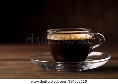 Cup of coffee with fume on the wooden background - stock photo