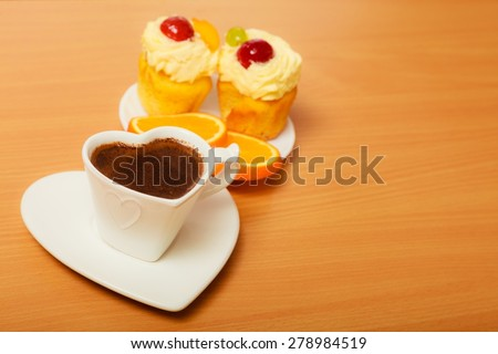Cup of coffee with gourmet delicious cookie cake with sweet cream and fruits as dessert food on top served with orange on plate. Breakfast on board. - stock photo