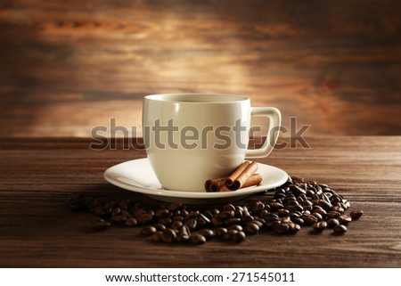 Cup of coffee with grains and cinnamon sticks on wooden background - stock photo