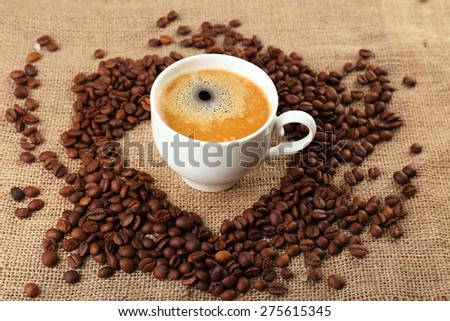 Cup of coffee with grains on burlap cloth background - stock photo