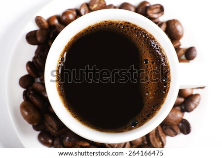 Cup of coffee with grains, top view - stock photo