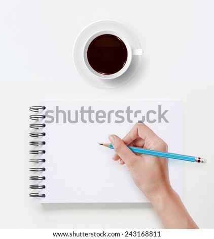 Cup of coffee with hand drawing on white notebook.