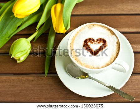 Cup of coffee with heart and yellow tulips - stock photo