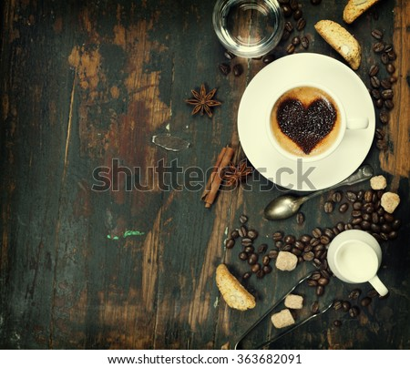 Cup of coffee with heart on foam and some ingredients - stock photo