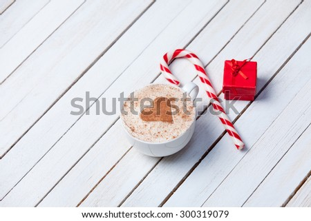Cup of coffee with heart shape and christmas candy near red gift on white wooden background.