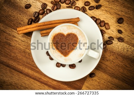 Cup of coffee with heart shape on foam served in porcelain saucer on wooden table. Shot from aerial view - stock photo