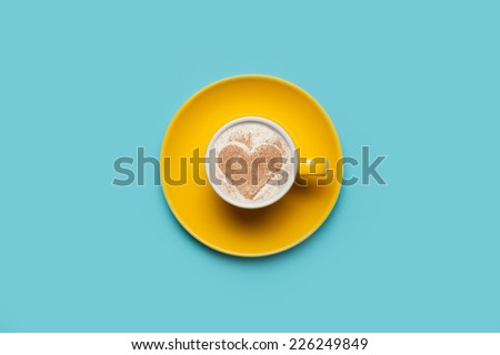 Cup of coffee with heart shape symbol on color background. - stock photo