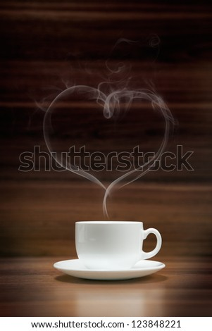 Cup of coffee with heart-shaped smoke on dark wood background - stock photo