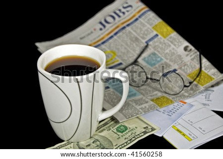 cup of coffee with job classifieds and bills - stock photo