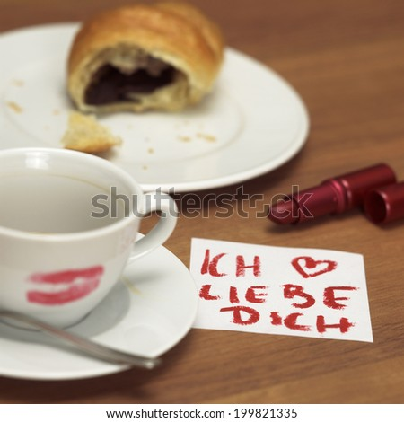 Cup of coffee with lipstick kiss, croissant and note - stock photo