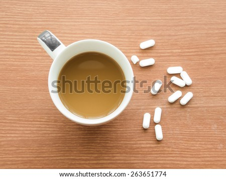 Cup of coffee with medicine pills